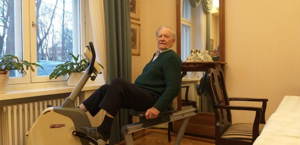 Äldre vit man sitter på en motionscykel