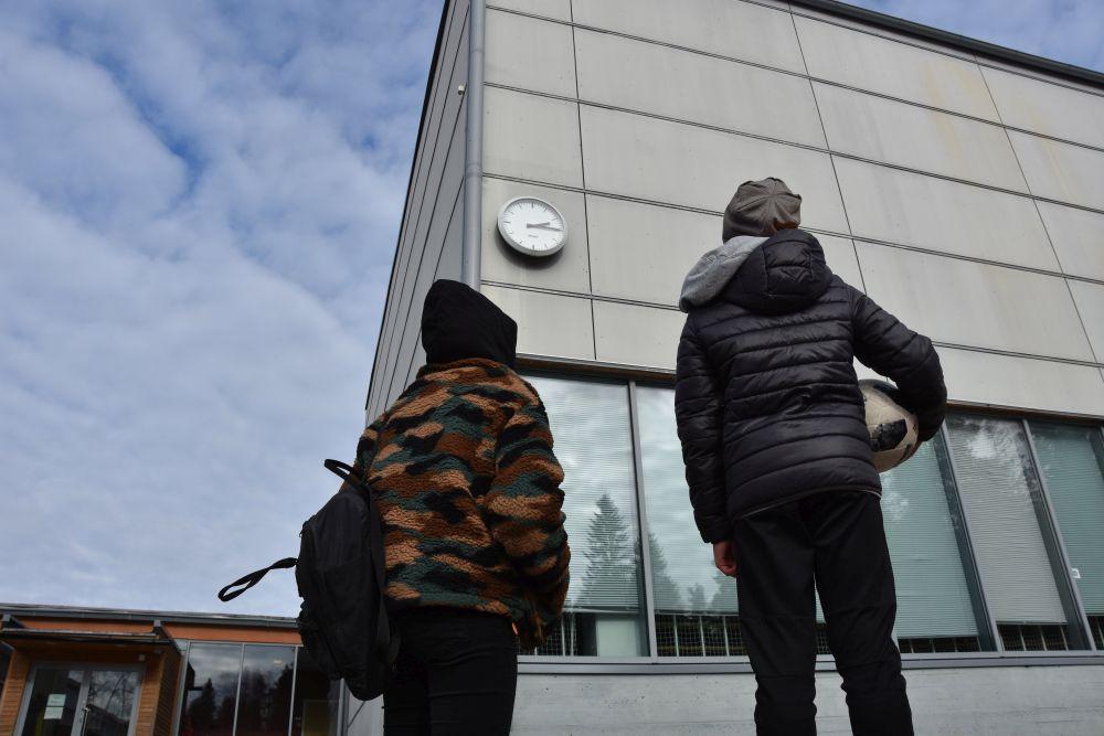 Två barn utanför en skolbyggnad.
