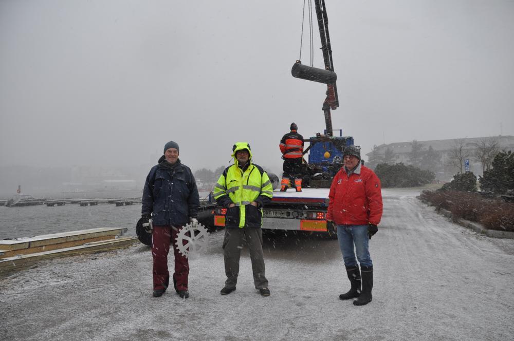 Tre män i snöväder framför en stor lastbil