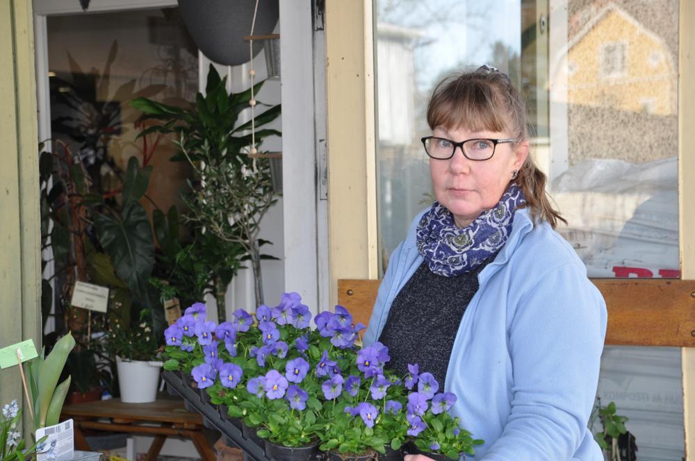 kvinna utanför trädgårdsaffär