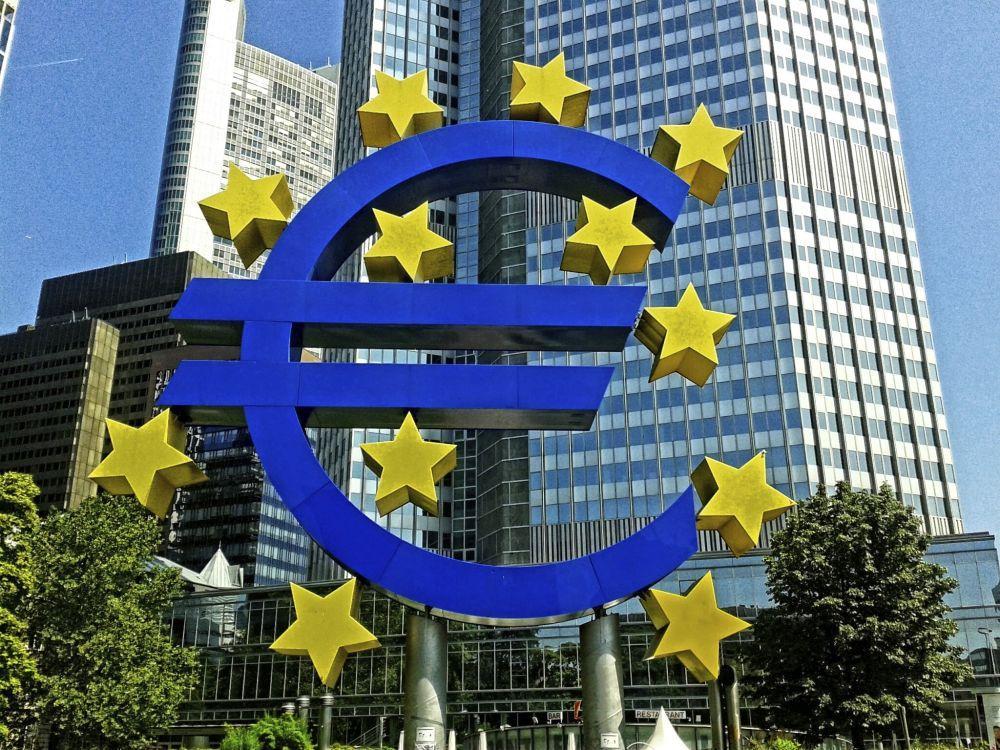 Eurosymbol på en bild med höga hus.