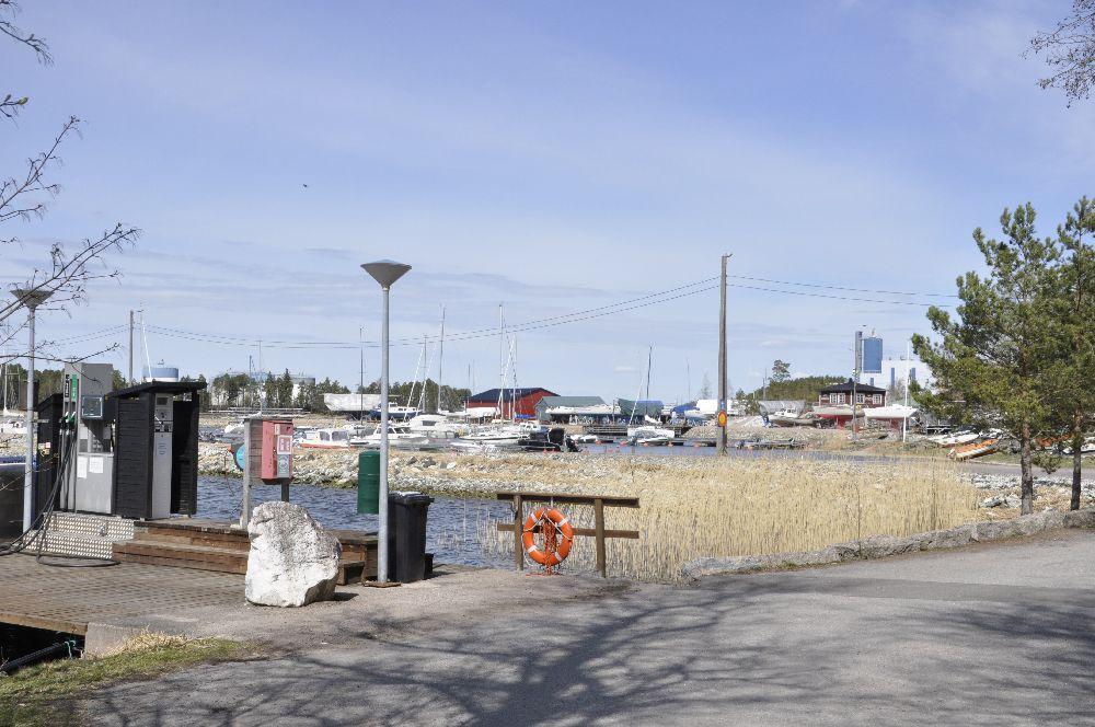 Naturskönt hamnområde. I förgrunden tankningsställe för båtar, längre bort syns bryggor, båtar och byggnader.