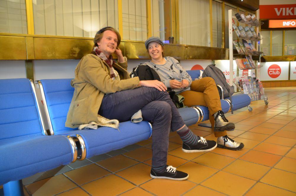 Två unga människor sitter på en bänk.