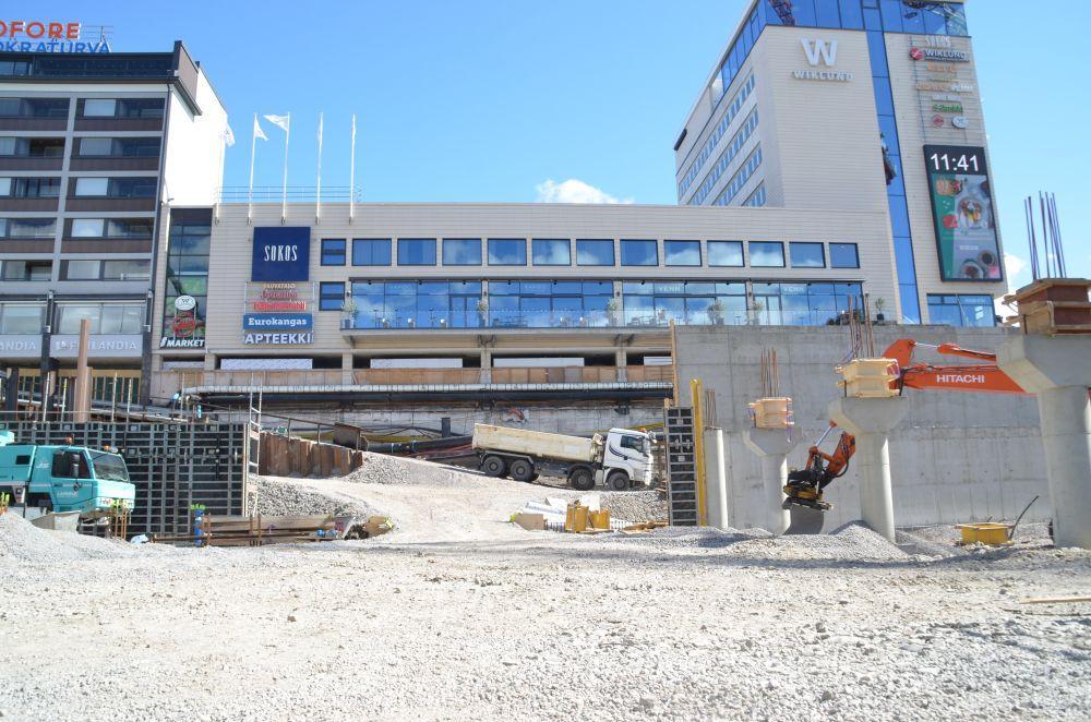 Byggarbetsplats med varuhus i bakgrunden.