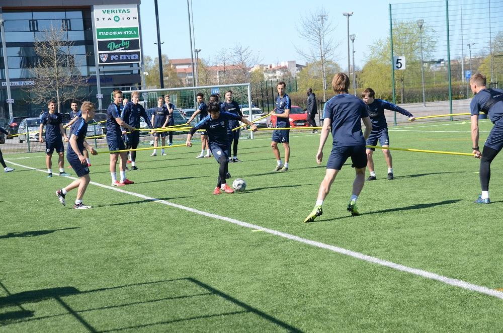 Fotbollsspelare håller i käppar när de tränar.