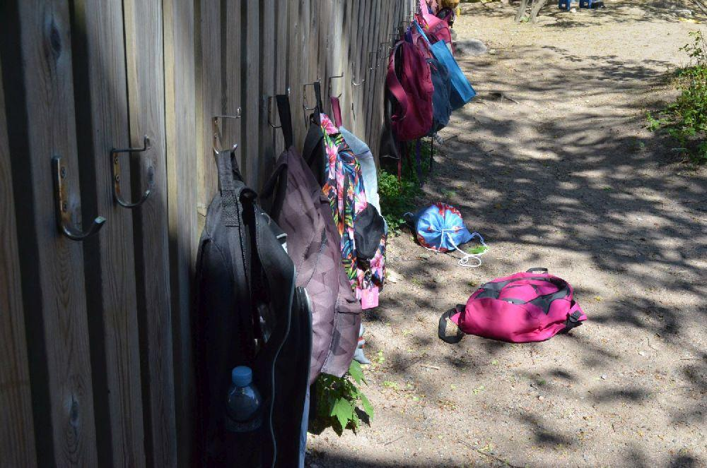 Ryggsäckar hänger på rad på ett staket