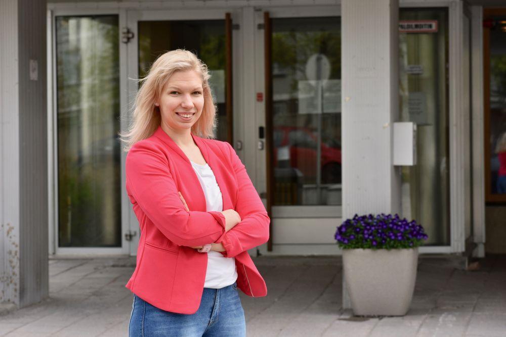 Porträtt av en kvinna som står framför en ingång till ett universitet.