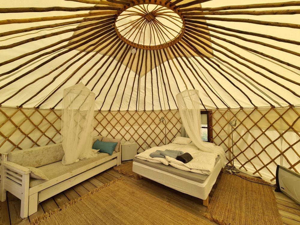 Insidan av ett stort tält med en säng och en soffa.