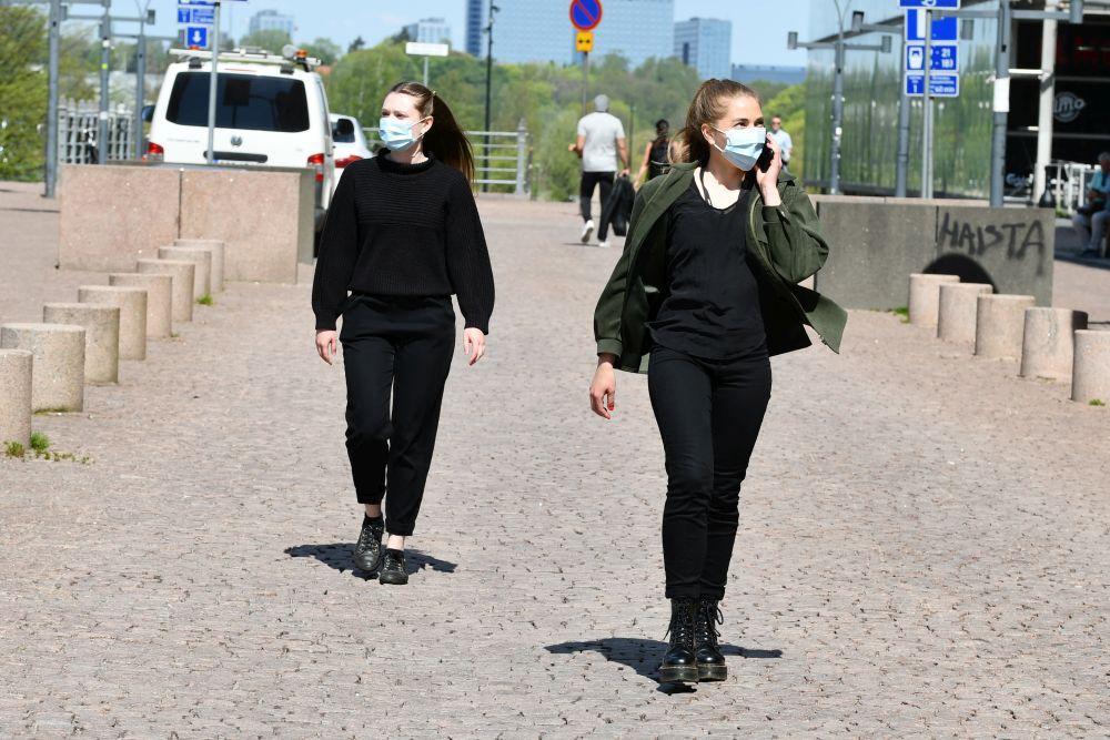 Två unga kvinnor går längs en kullerstensgata iklädda munskydd.