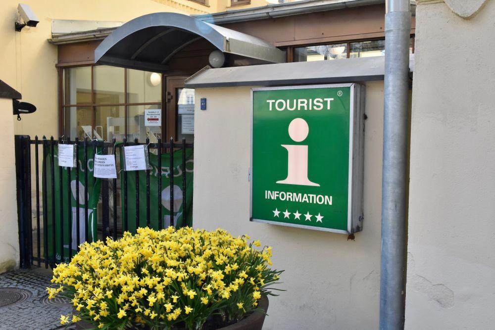 """Ingången till en turistinformation med en gul blomma och en grön skylt med texten """"turist information""""."""