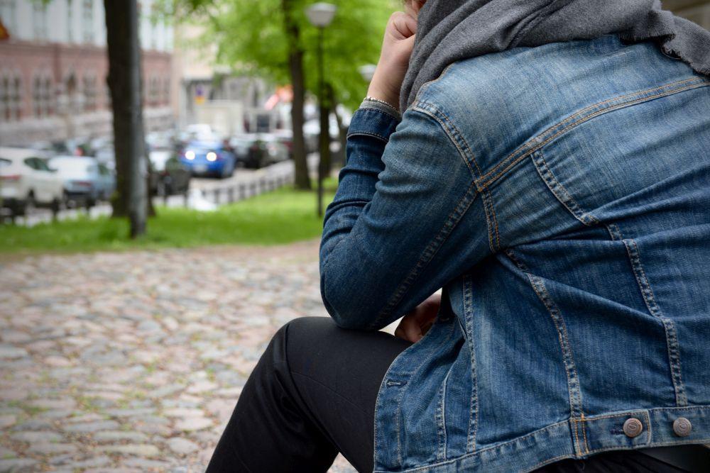 person i jeansjacka sitter i park med ryggen mot kameran.