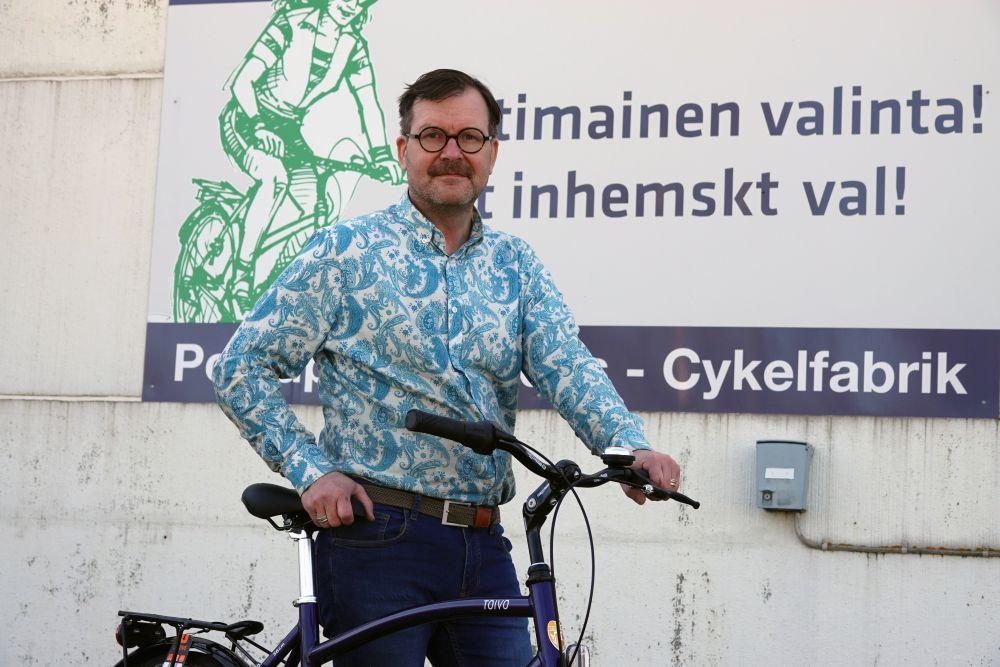man står och håller i cykel.