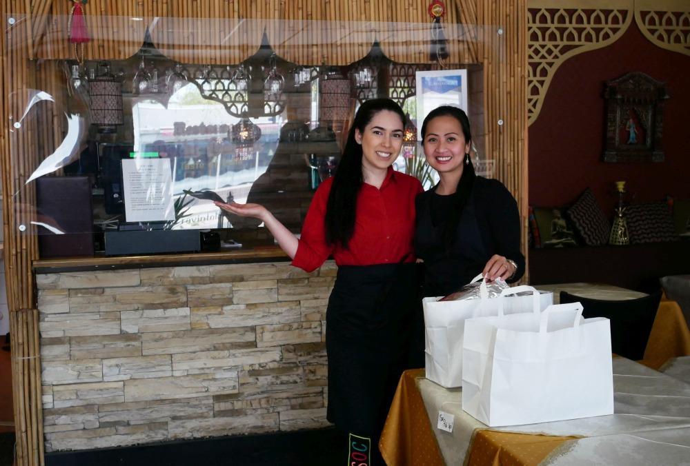två damer i indisk restaurang poserar framför hämtmatspåsar