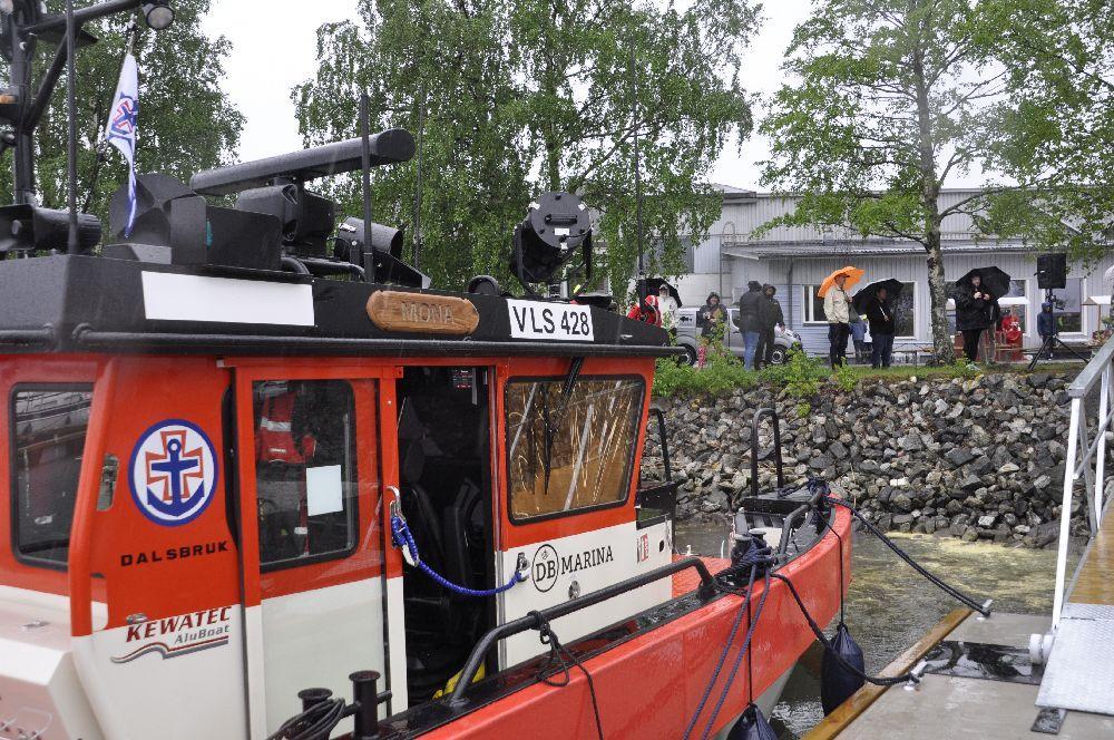 Sjöräddningsbåt snett bakifrån. Folk med paraplyn syns ovanför hamnen
