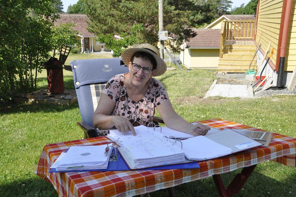 Dam sitter utomhus vid ett bord där det ligger flera stora mappar
