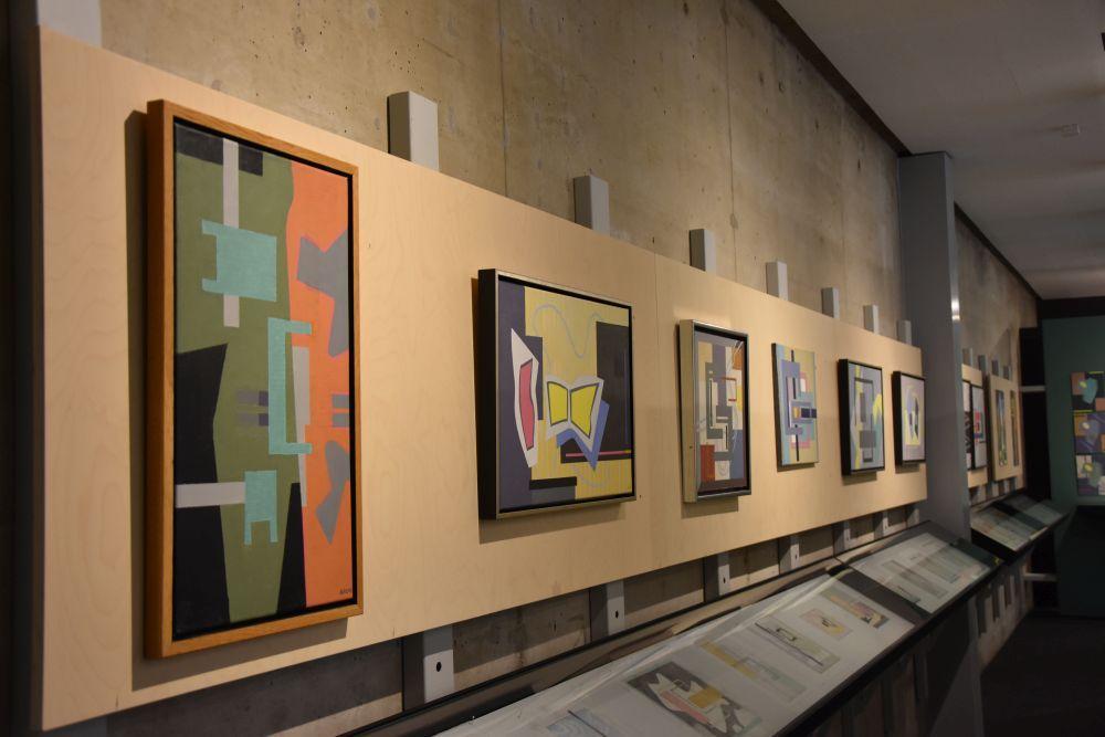 Färggranna och geometriska abstrakta målningar upphängda på en vägg.