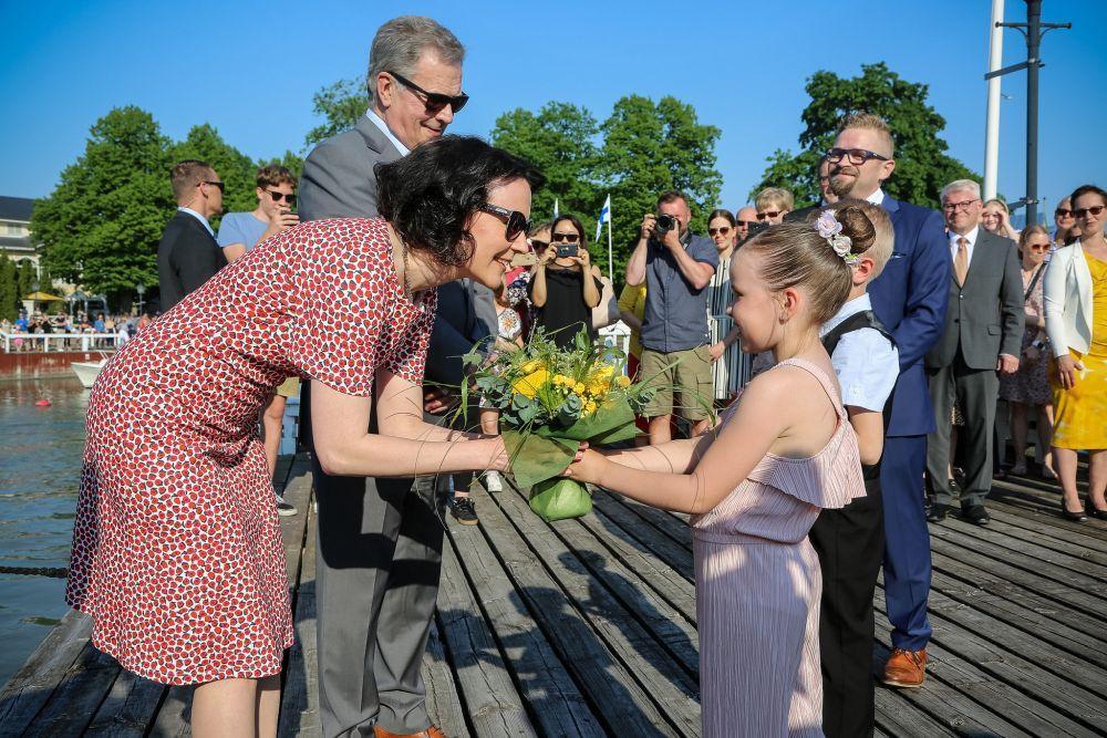 Presidentparet får blommor av två skolelever