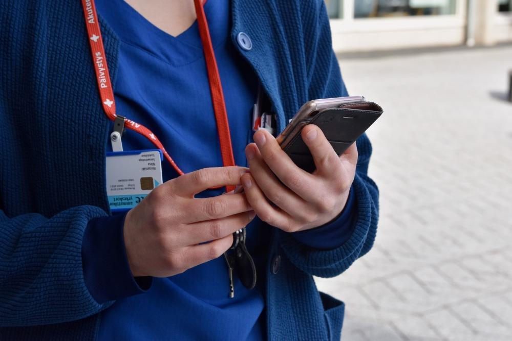 sjukvårdare håller i mobiltelefon