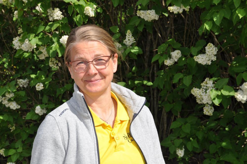 Kvinna med gul t-skjorta och grå tröja