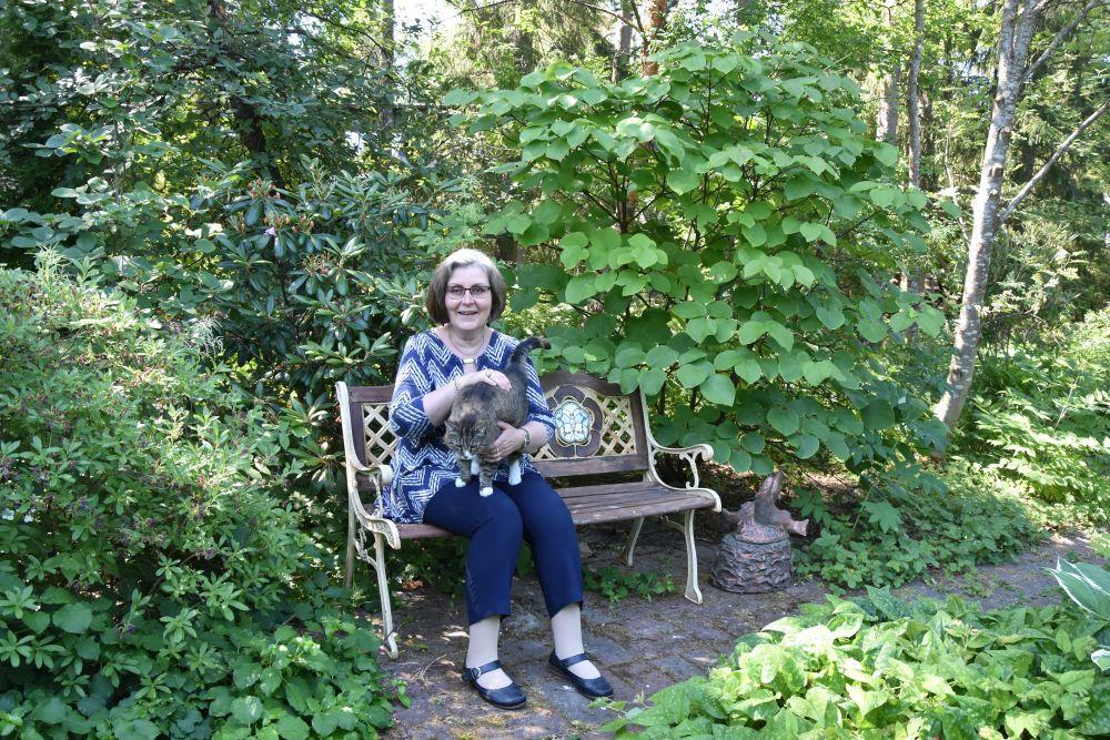 En kvinna sitter utomhus med katt.
