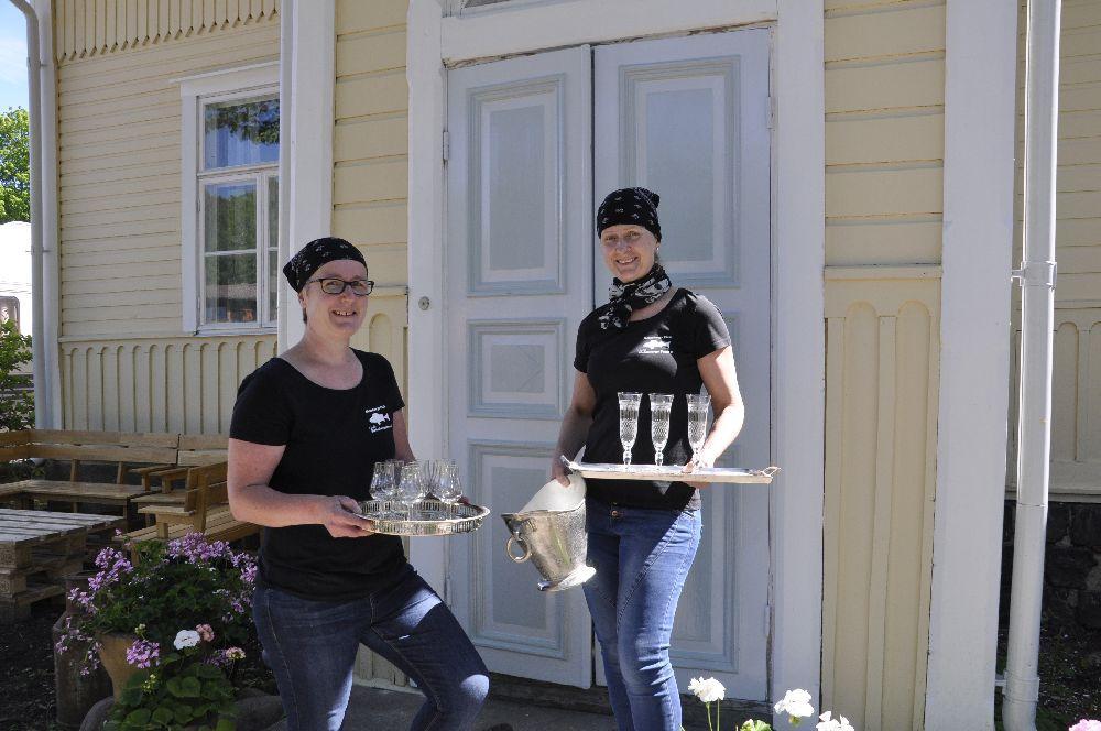 Två damer vid en nymålad dörr. I händerna har de glas och brickor.
