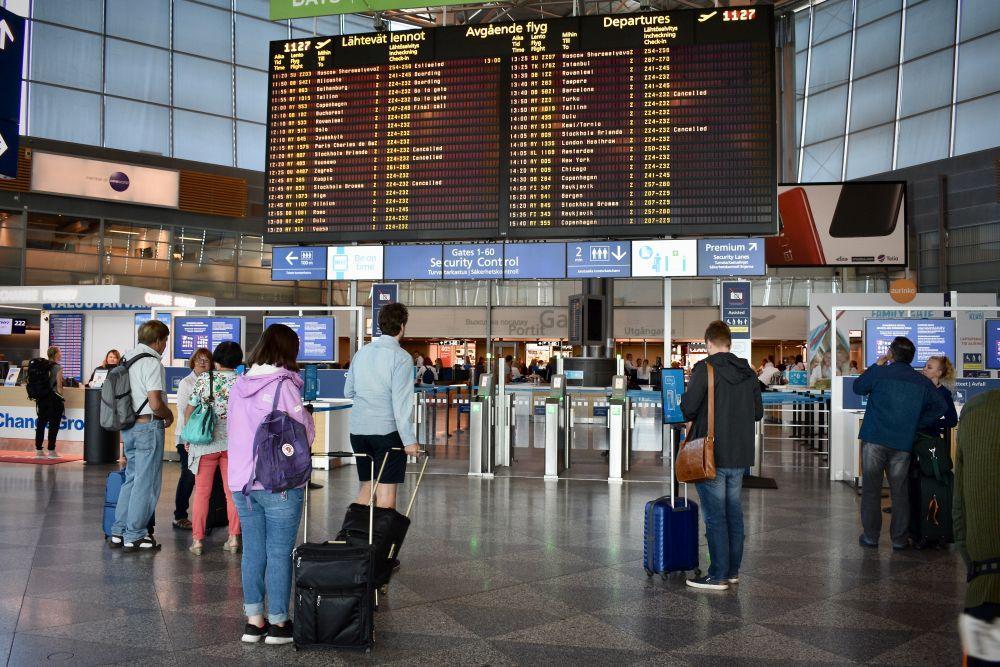Resenärer står och kollar på skärm med information om avgående flyg på flygfältet.