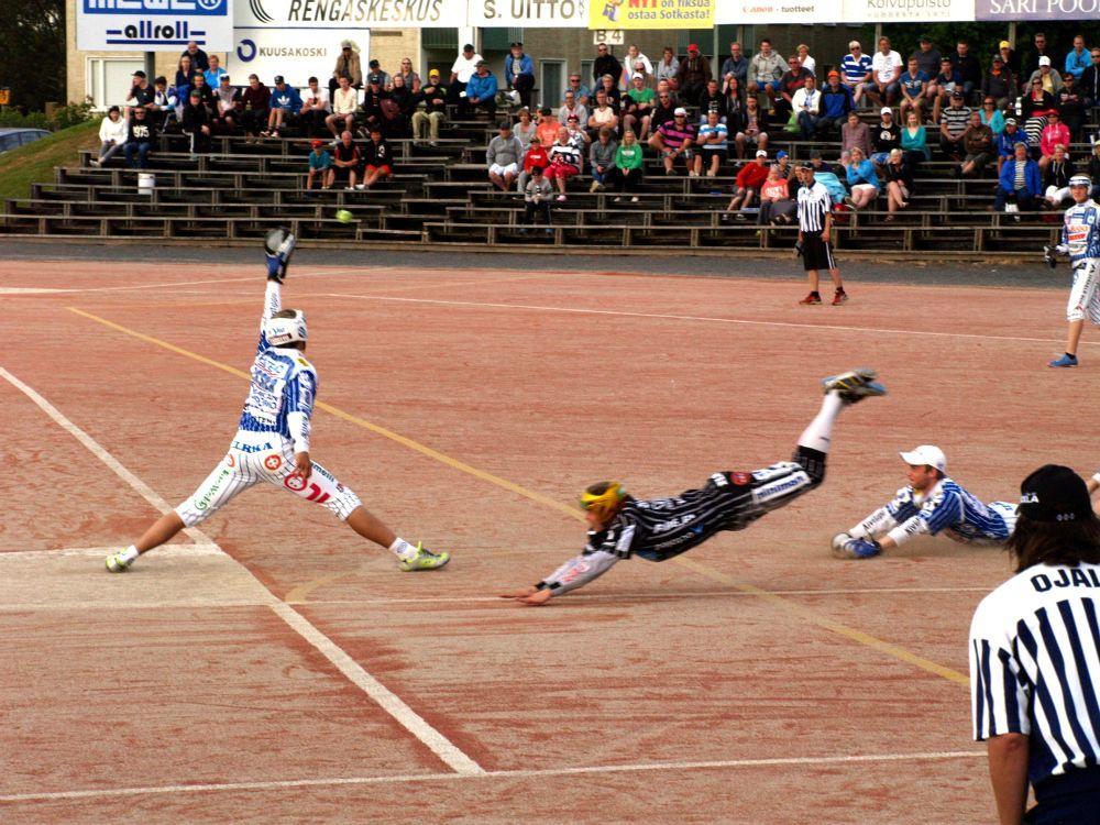 En sandplan där en person klädd i vitt hoppar för att fånga en boll och en svartklädd person precis ska landa på mage.