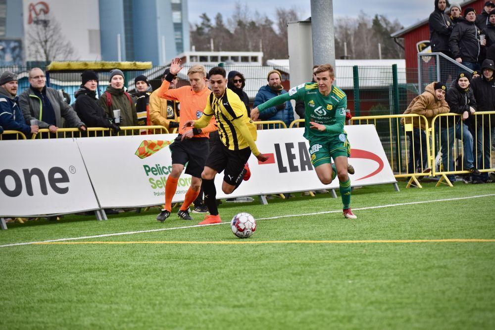 Två manliga fotbollsspelare, en i gul tröja och en i grön, jagar en boll på en fotbollsplan.