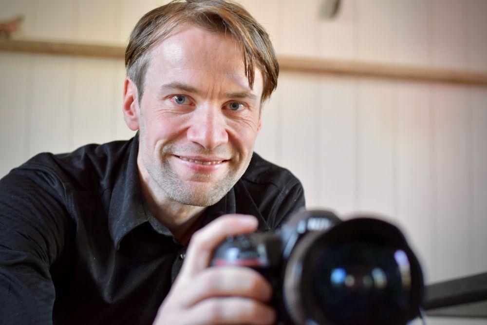 Porträtt av en leende man som håller i en kamera.