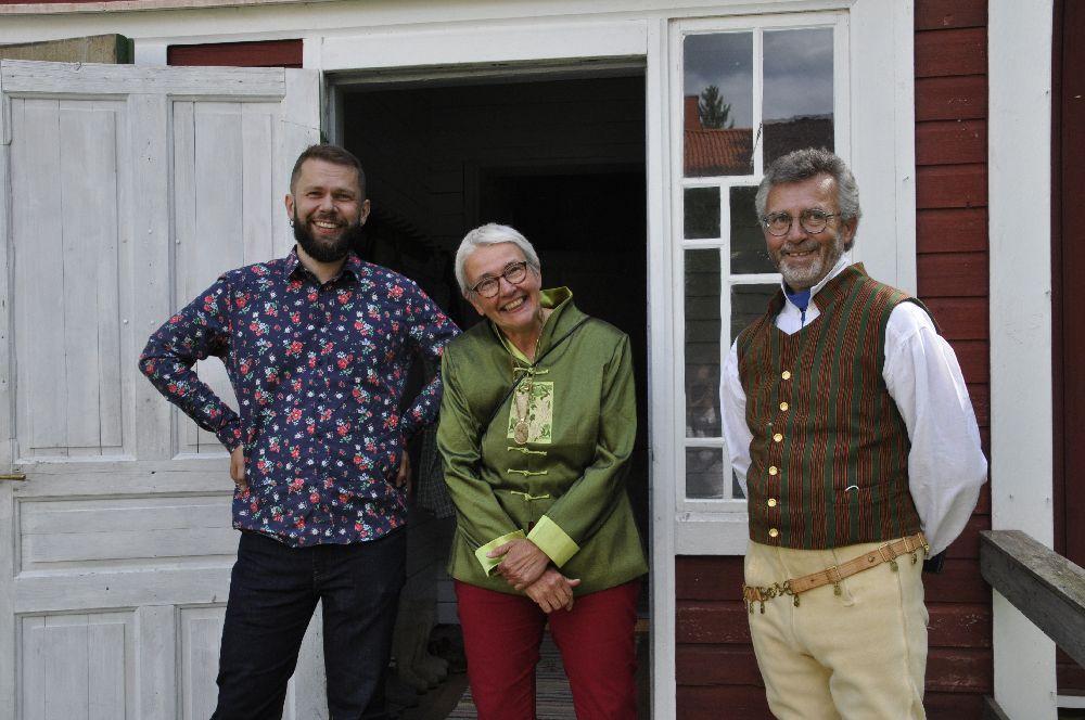 Tre personer på en veranda till ett gammalt rött trähus