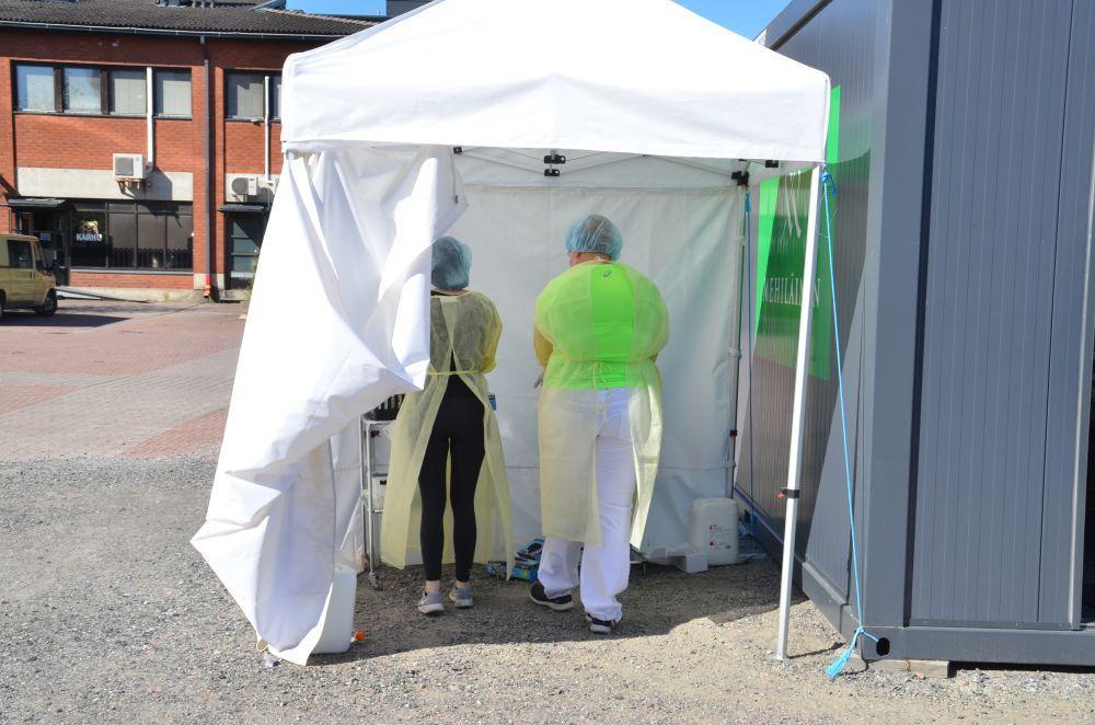 Laboratorieskötare i ett testbås utomhus.