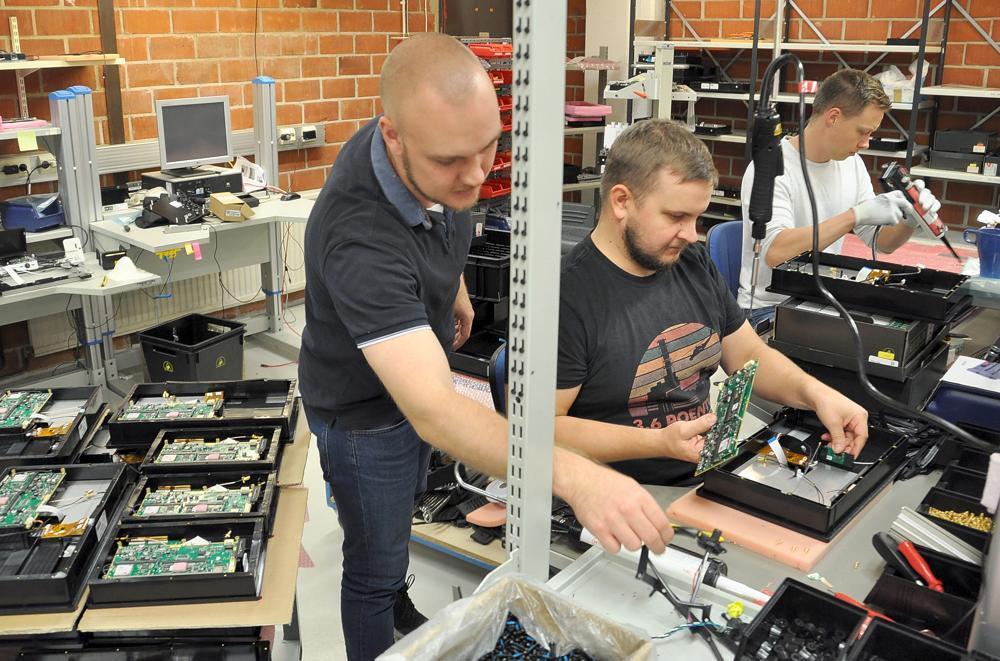 tre män monterar elektronikkomponenter