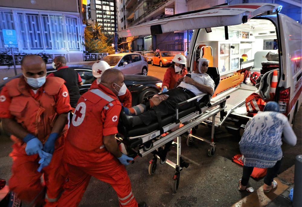 Personal från Röda Korset hjälper en skadad man in i en ambulans.