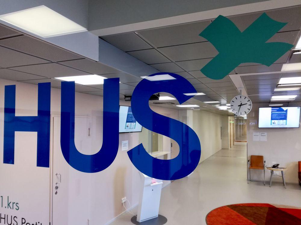 En glasvägg i ett sjukhus i Helsingfors med texten HUS.