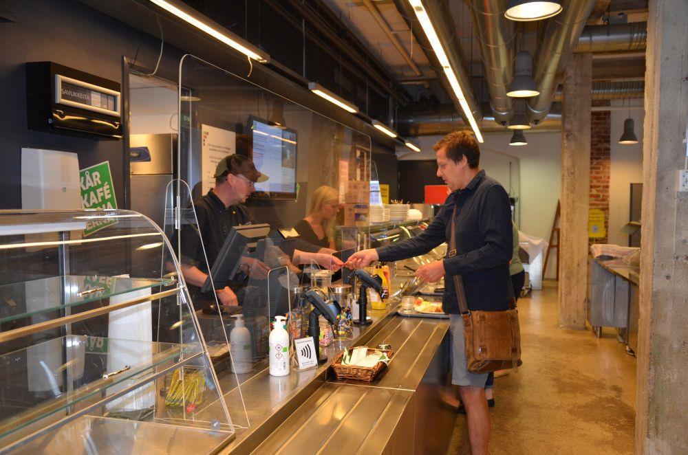 Lunchkön i Café Arken. En man betalar precis för sin lunch. Ett plexiglas skiljer honom från personalen bakom disken.