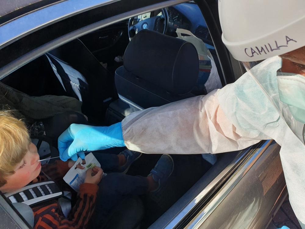 vårdpersonal sticker in provsticka genom bilruta, tar nässvalgprov på ett barn