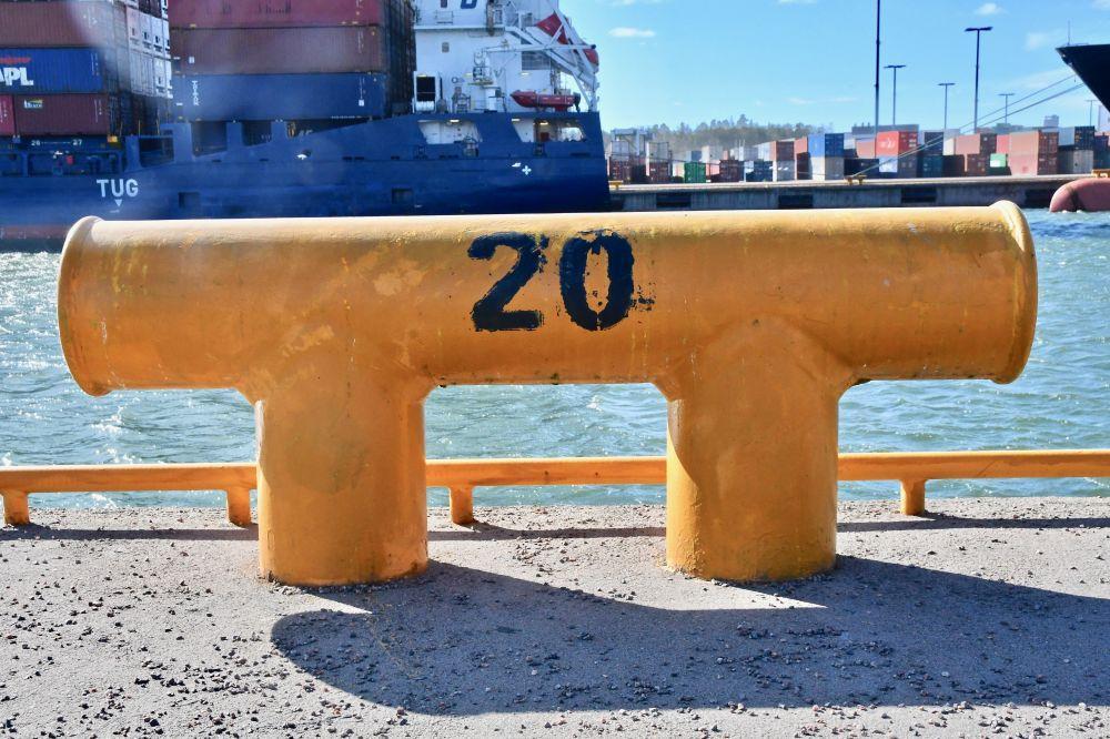 En pollare i gult i en stor hamn.