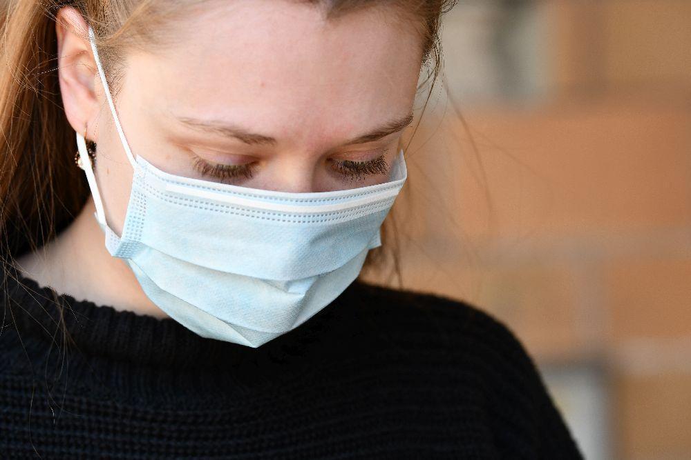 Närbild av kvinna med munskydd.
