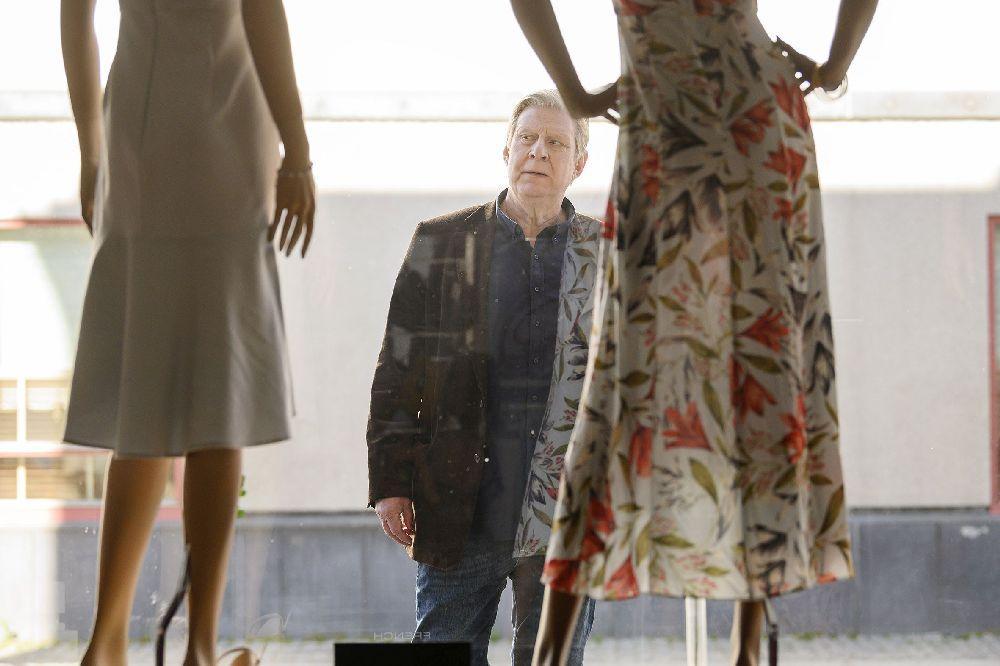två kvinnor stå med ryggen åt kameran. En man betraktar dem.