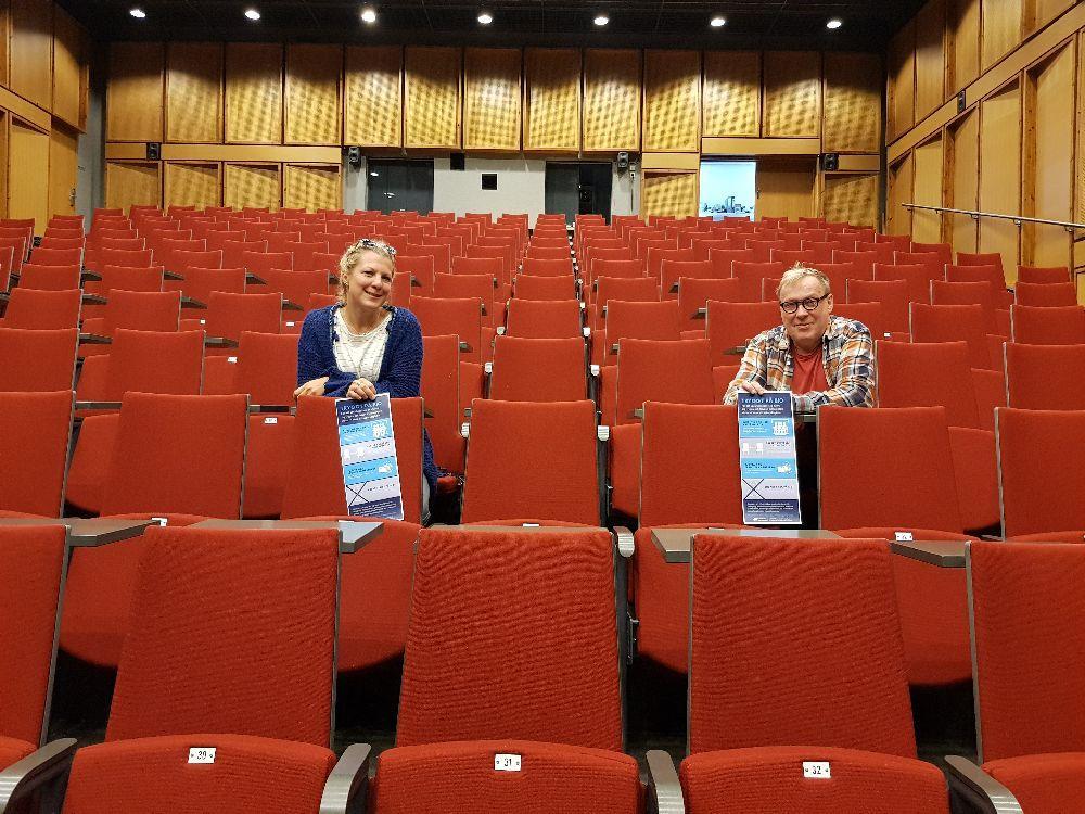 Två personer i ett auditorium med röda stolar