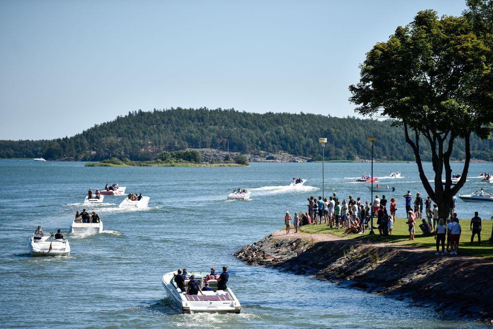 Flera båtar kör i rad efter varandra runt en udde