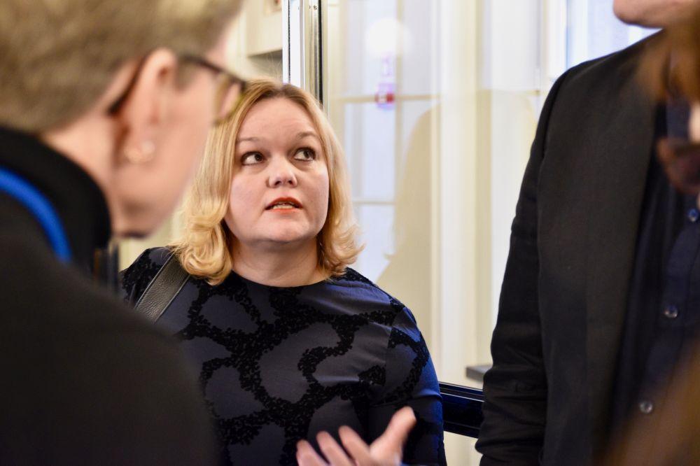 Blond kvinna pratar med ett par människor.