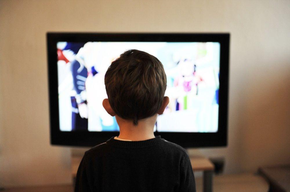 Barn sitter framför skärm