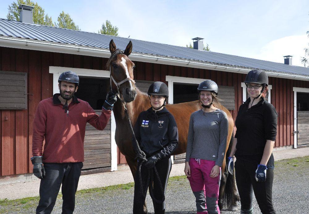 Fyra personer i hjälm står kring en häst.