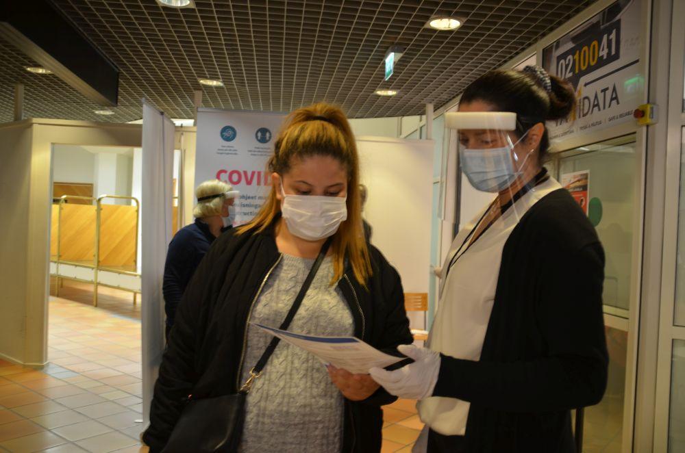 Två kvinnor med munskydd talar med varandra.