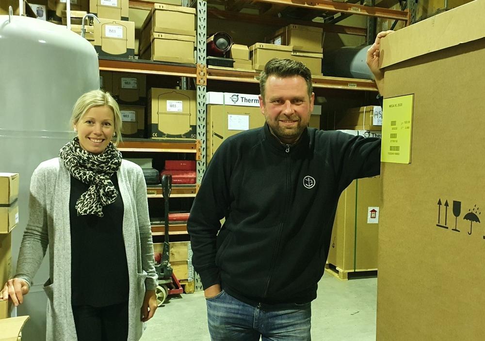 kvinna och man står i en lagerhall med stora förpackningar runt sig