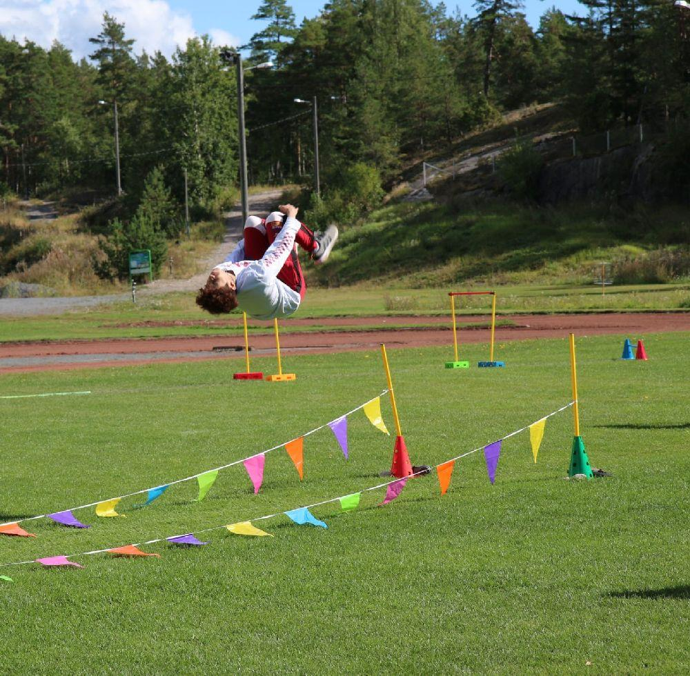 pojke gör volt i luften på en idrottsplan